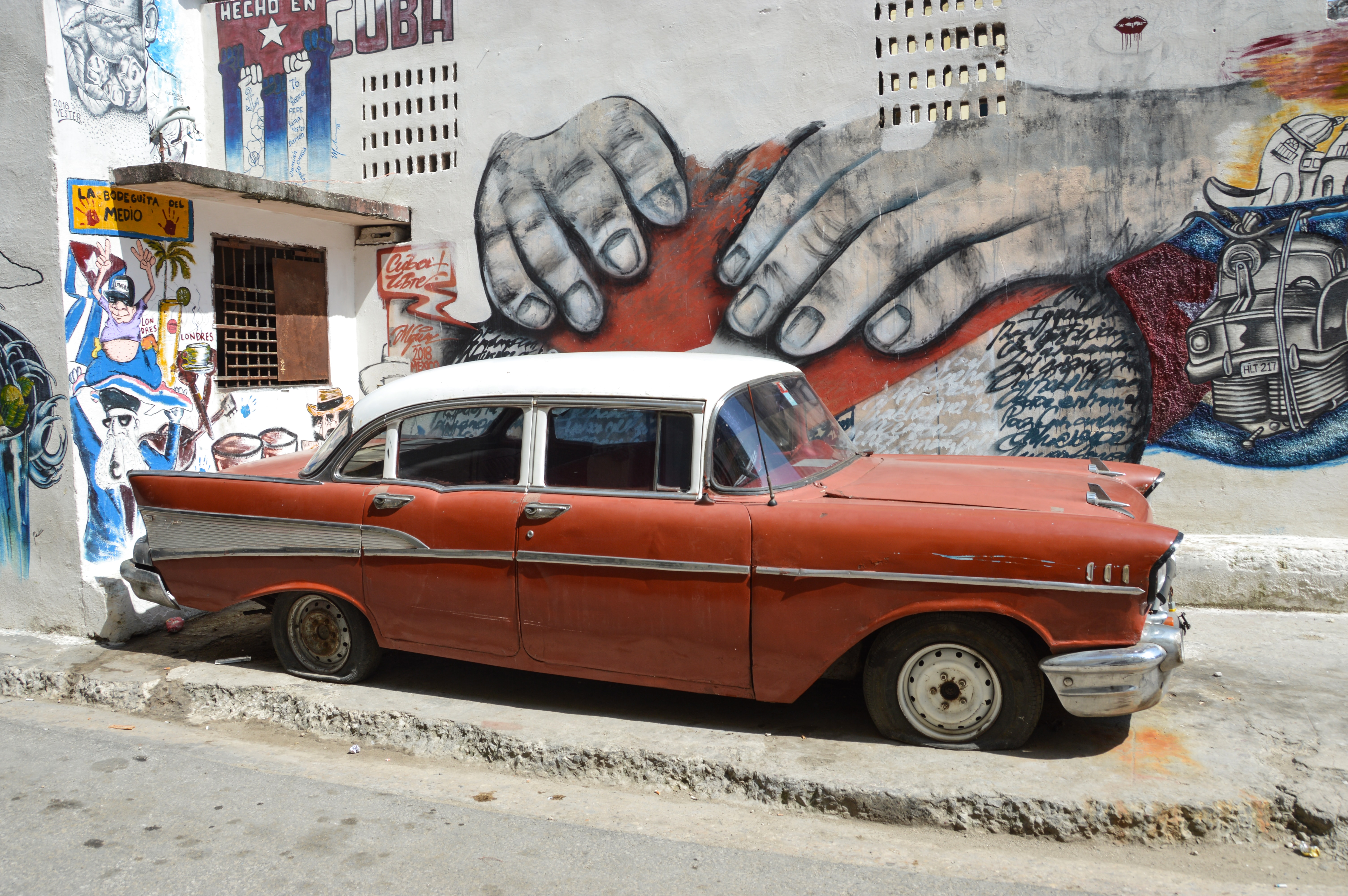 white and red sedan parked near wall with mural